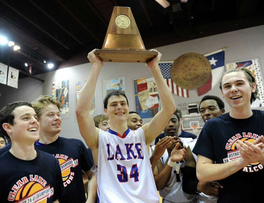 Clear Lake guard Chris Stenerson (34) hoists the champion's trophy after the 6A Region 3 high school boys basketball final against Clear Creek, Saturday, March 7, 2015, at Campbell Center in Houston. Clear Lake won the game, 63-56. Photo: Eric Christian Smith, For The Chronicle / 2015 Eric Christian Smith