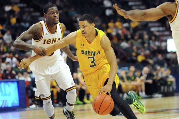 Siena's Ryan Oliver, center, drives the ball as Iona's A.J. English defends during their quarterfinal game of the MAAC Championship on Saturday, March 7, 2015, at Times Union Center in Albany, N.Y. (Cindy Schultz / Times Union) Photo: Cindy Schultz / 00030912A
