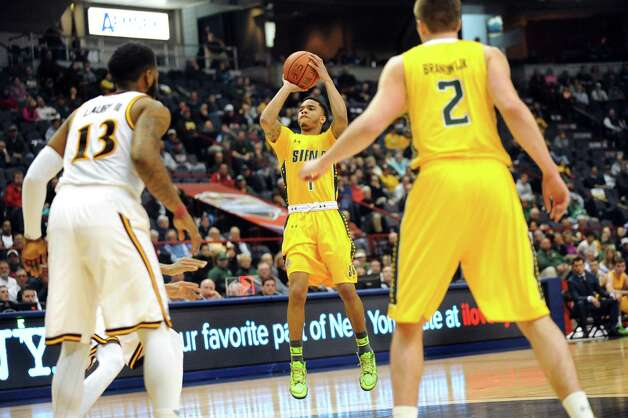 Siena's Marquis Wright, center, takes a three-point shot during their quarterfinal game against Iona in the MAAC Championship on Saturday, March 7, 2015, at Times Union Center in Albany, N.Y. (Cindy Schultz / Times Union) Photo: Cindy Schultz / 00030912A