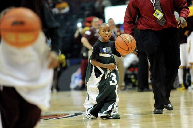 Dressed in an oversized uniform, a boy tries to dribble to the end of the court in a timeout contest during the quarterfinal game between Siena and Iona in the MAAC Championship on Saturday, March 7, 2015, at Times Union Center in Albany, N.Y. (Cindy Schultz / Times Union) Photo: Cindy Schultz / 00030912A
