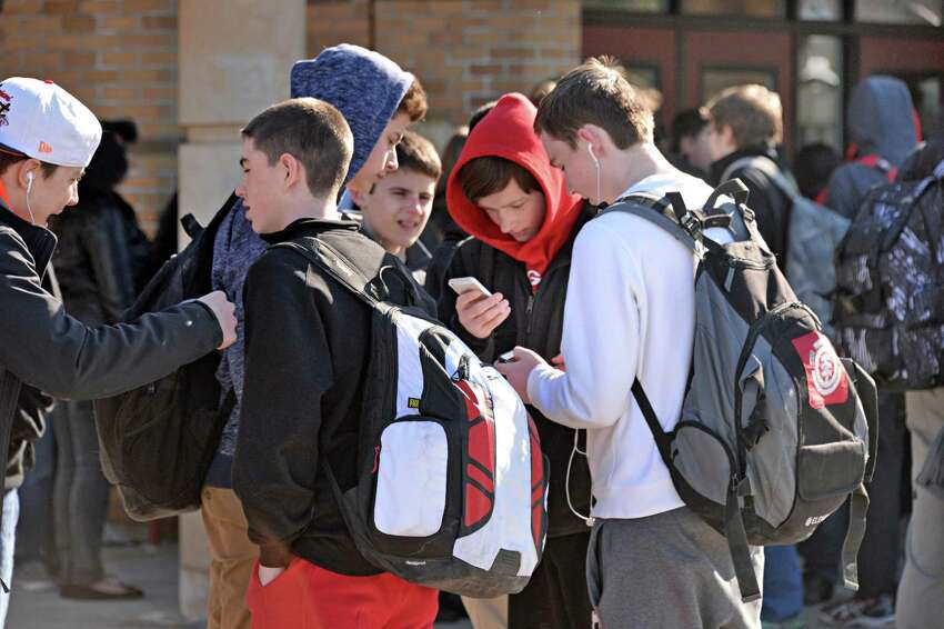 Students use their smart phones while waiting for their bus at Guilderland High School Friday March 6, 2015, in Guilderland Center, NY. (John Carl D'Annibale / Times Union)