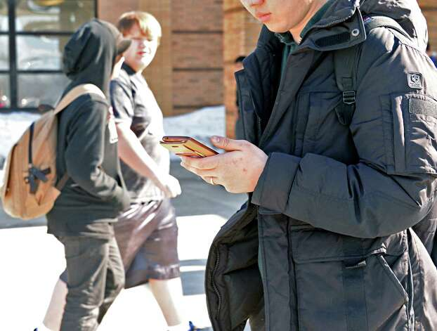 A student uses his smart phone outside Guilderland High after school Friday March 6, 2015, in Guilderland Center, NY.  (John Carl D'Annibale / Times Union) Photo: John Carl D'Annibale / 00030916A