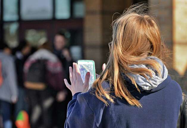 A student uses her smart phone outside Guilderland High School Friday March 6, 2015, in Guilderland Center, NY.  (John Carl D'Annibale / Times Union) Photo: John Carl D'Annibale / 00030916A