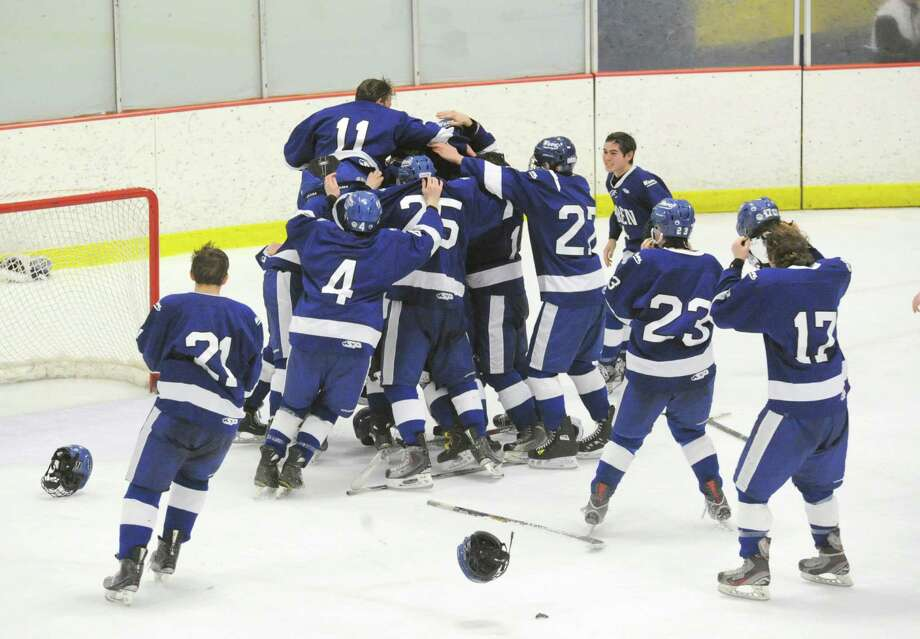 Darien's Nicholas Tuzinkiewicz (#11) occupies the top of the Darien High School boys hockey team victory pile at the conclusion of the FCIAC boys hockey championship game between Greenwich High School and Darien High School at Terry Conners Rink in Stamford, Conn., Saturday, March 7, 2015. Darien took the championship with a 5-3 victory. Photo: Bob Luckey / Greenwich Time