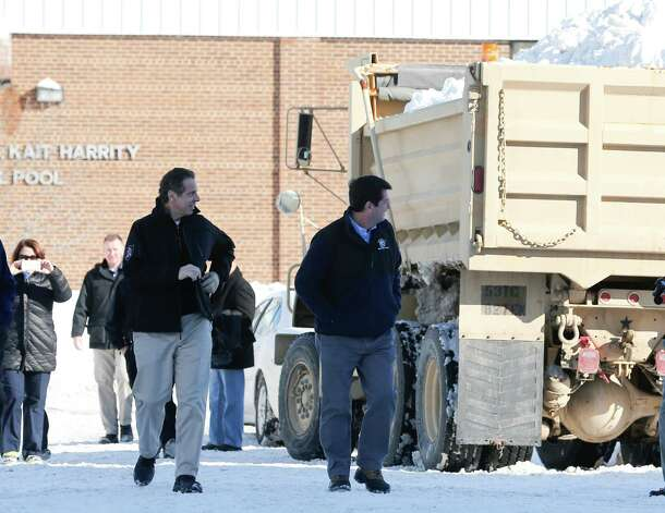 New York Gov. Andrew Cuomo, left, and Erie County Executive Mark Poloncarz walk past a New York National Guard truck loaded with snow in the south Buffalo area on Nov. 21, 2014, in Buffalo. (AP Photo/Mike Groll) ORG XMIT: NYMG116 Photo: Mike Groll / AP