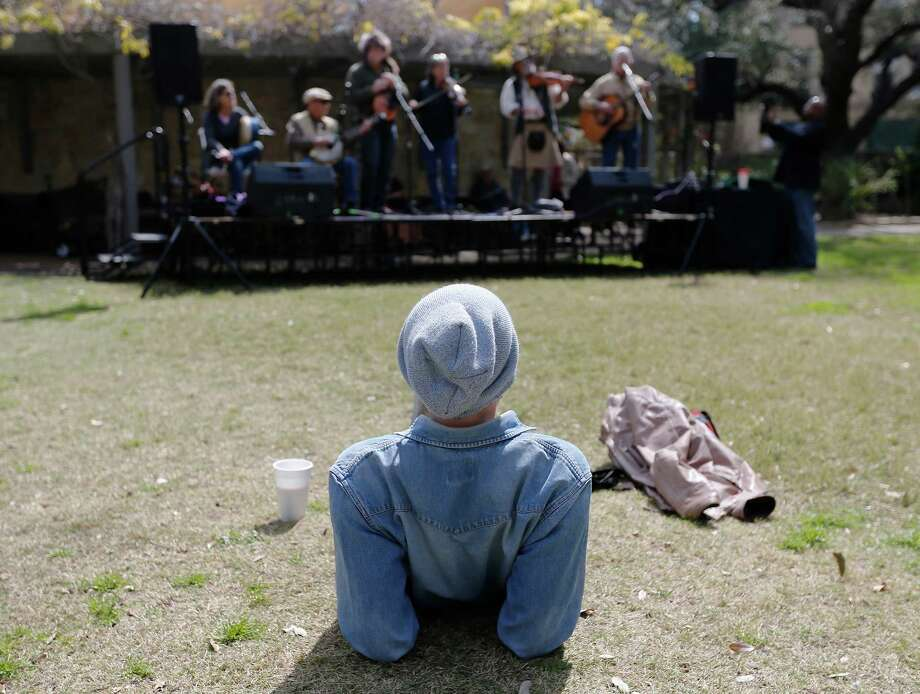 Alex Nee from San Francisco, California takes in a performance by the group, Rupert's Revenge, at the second annual Crockett Fiddlers' Festival at the Alamo on Saturday, Mar. 7, 2015. Celtaire was one of several bands performing on the grounds of the Alamo where David Crockett was alleged to have played a fiddle during his role as one of the defenders of the hallowed mission. The music played on Saturday were accompanied by the loud booms of cannon fire and musket discharges by re-enactors taking part in the historical remembrance of the battle at the Alamo. (Kin Man Hui/San Antonio Express-News) Photo: Kin Man Hui / ©2015 San Antonio Express-News