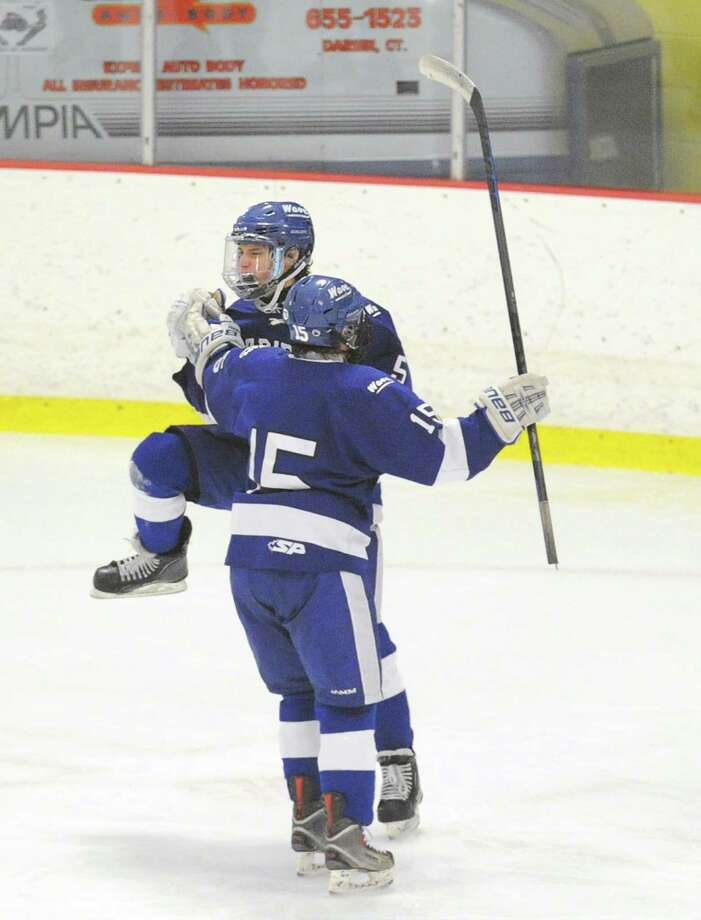 Darien High School  hockey players Craig Miller (#15), foreground, and Jake Kirby (#5) background celebrate a Kirby goal, the fourth and what turned out to be the winning goal of the game for Darien during FCIAC boys hockey championship game between Greenwich High School and Darien High School at Terry Conners Rink in Stamford, Conn., Saturday, March 7, 2015. Darien took the championship with a 5-3 victory. Photo: Bob Luckey / Greenwich Time