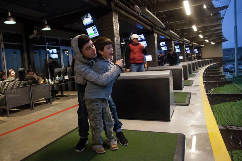 Manuel Giraldo, 16, helps his little brother Nicolas Miranda-Garcia, 6, hit the ball at Top Golf, which opened last year at The Rim shopping center. The business is one of many clustered along Interstate 10, which is slated for expansion. Photo: Julysa Sosa /For The San Antonio Express-News / Julysa Sosa For the San Antonio Express-News