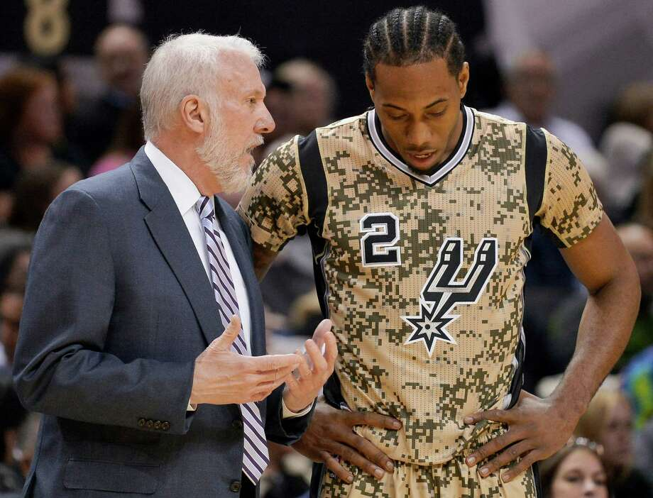 San Antonio Spurs coach Gregg Popovich, left, talks to forward Kawhi Leonard during the first half of an NBA basketball game against the Denver Nuggets, Friday, March 6, 2015, in San Antonio. The Spurs won 120-111. (AP Photo/Darren Abate) Photo: Darren Abate, FRE / Associated Press / FR115 AP