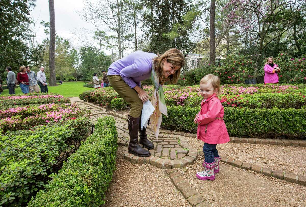 Volunteer Carson Seeligson tells 2-1/2-year-old Amanda Griffin about the Butterfly Garden Saturday March 7, 2015