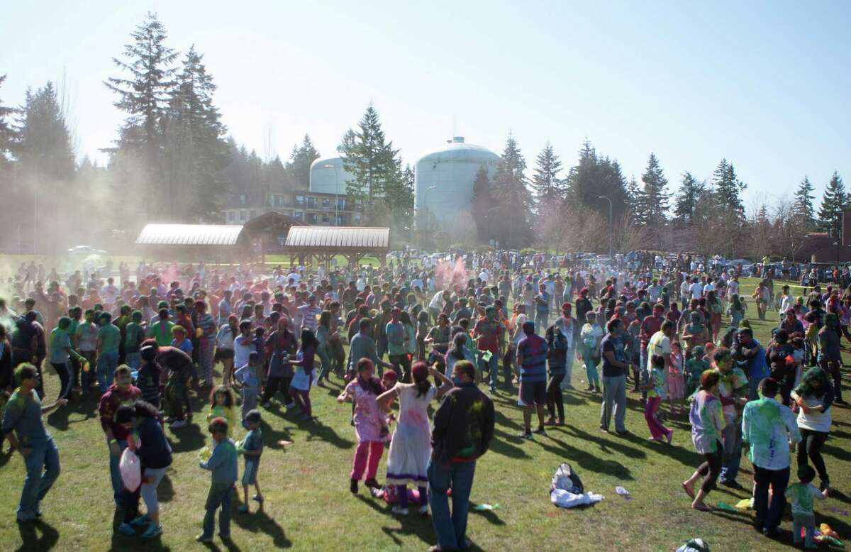 Clouds of dust rise from the crown at the annual Holi festival at Crossroads Park in Bellevue. During Holi, people gather to welcome the arrival of spring and toss colored powder in celebration. This festival is also a fundraiser for CRY, a child rights organization. Photographed on Saturday, March 7, 2015.