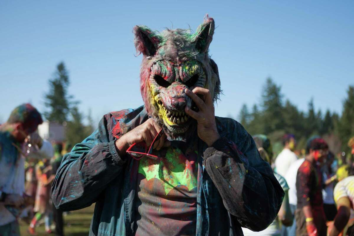 Amit Deo hides behind a wolf mask while celebrating the annual Holi festival at Crossroads Park in Bellevue. During Holi, people gather to welcome the arrival of spring and toss colored powder in celebration. This festival is also a fundraiser for CRY, a child rights organization. Photographed on Saturday, March 7, 2015.