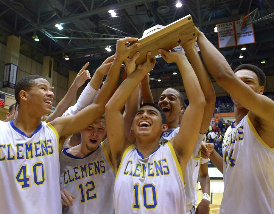 Clemens basketball team members hold up their trophy after defeating Laredo Alexander for the Region IV-6A championship at the UTSA Convocation Center on March 7, 2015. Photo: Billy Calzada /San Antonio Express-News / San Antonio Express-News