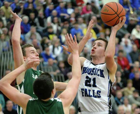 Hoosick Falls' #21 Austin Pitt, right, gets a shot off over Shalmont defenders during the Class B boys' basketball final at Colonie High School Saturday March 7, 2015 in Colonie, NY.  (John Carl D'Annibale / Times Union) Photo: John Carl D'Annibale / 00030907A