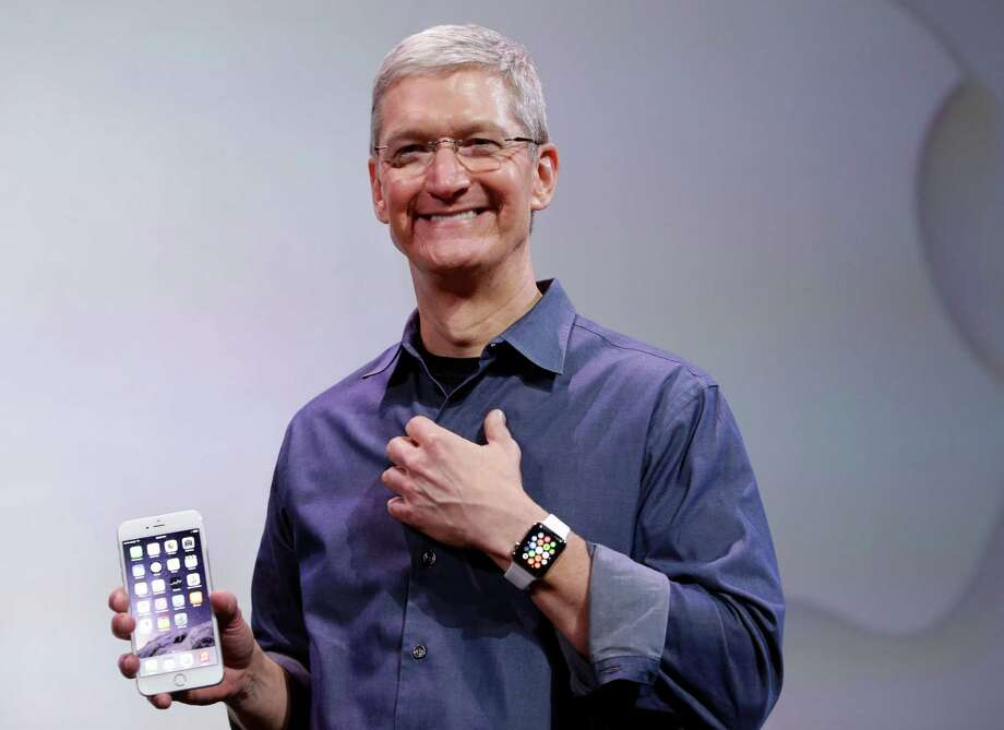 Apple CEO Tim Cook, holding an iPhone 6 Plus and wearing an Apple Watch, has hinted the Apple Watch will be as game-changing as Apple's revolutionary iPhones and iPads, which have become indispensable accessories for millions around the globe. Photo: Associated Press File Photo / AP
