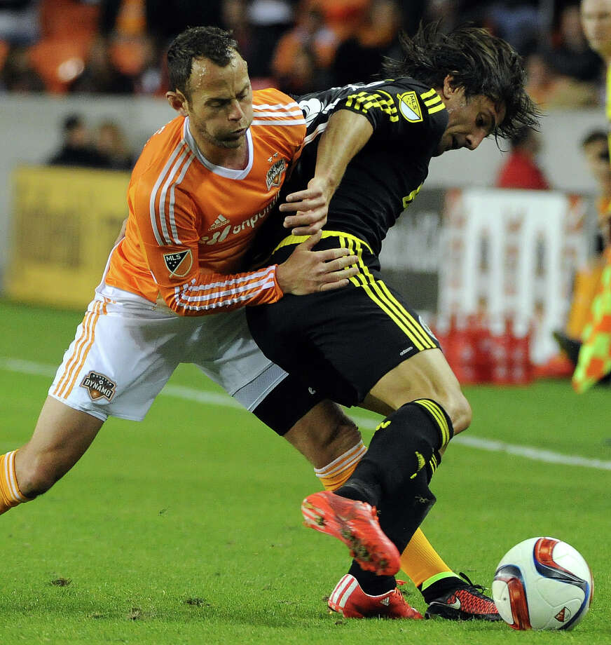 Houston Dynamo midfielder Brad Davis, left, fights for possession with Columbus Crew defenseman Hernan Grana during the first half of an MLS soccer game, Saturday, March 7, 2015, at BBVA Compas Stadium in Houston. Photo: Eric Christian Smith, For The Chronicle / 2015 Eric Christian Smith