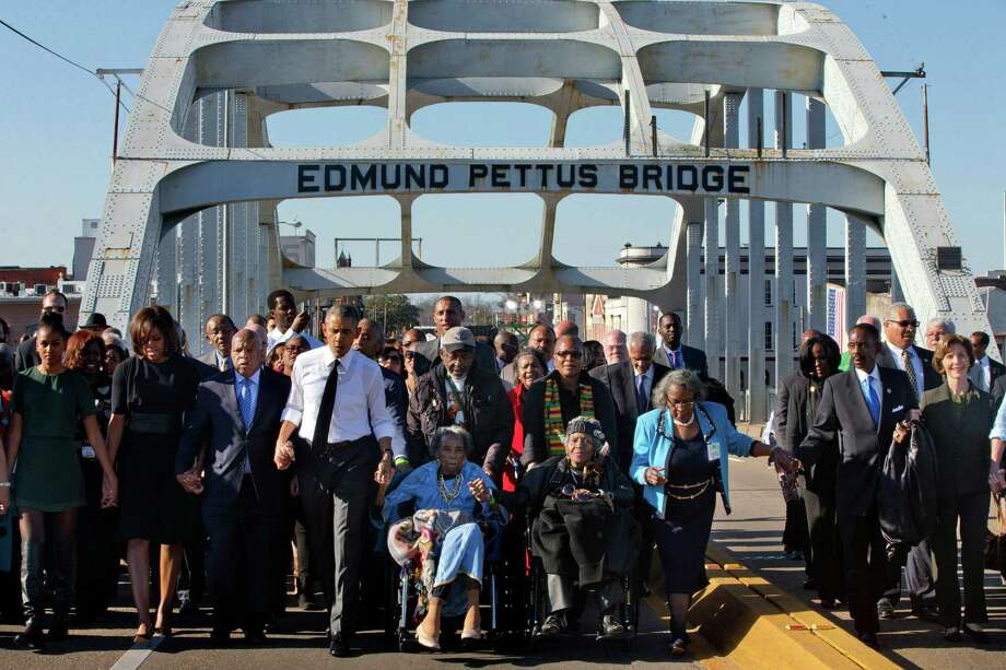 """President Barack Obama, fourth from left, walks holding hands with Amelia Boynton Robinson, who was beaten during """"Bloody Sunday,"""" as they and the first family and others including Rep. John Lewis, D-Ga, left of Obama, walk across the Edmund Pettus Bridge in Selma, Ala,. for the 50th anniversary of the landmark event of the civil rights movement, Saturday, March 7, 2015. At far left is Sasha Obama and at far right is former first lady Laura Bush. Adelaide Sanford also sits in a wheelchair. (AP Photo/Jacquelyn Martin) Photo: Jacquelyn Martin, Associated Press / AP"""