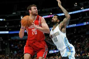 Houston Rockets forward Donatas Montiejunas, left, of Lithuania, looks for a shot in front of Denver Nuggets forward Wilson Chandler in the first quarter of an NBA basketball game Saturday, March 7, 2015, in Denver. (AP Photo/David Zalubowski)