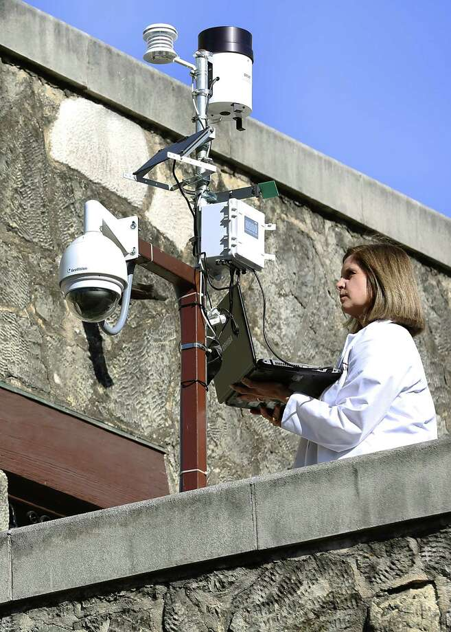 Pamela Jary Rosser Conservator at the Alamo, hooks a laptop to the weather station located on the roof of the Gift Shop.  Thursday, Feb. 19, 2015. Photo: Bob Owen, Staff / San Antonio Express-News / © 2015 San Antonio Express-News