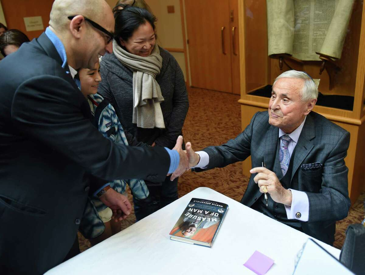 Holocaust survivor Martin Greenfield, right, signs a copy of his book for Greenwich residents Chetan Bhandari, left, Ivy Bhandari, 11, and Debi Bhandari after Greenfield spoke in a program called