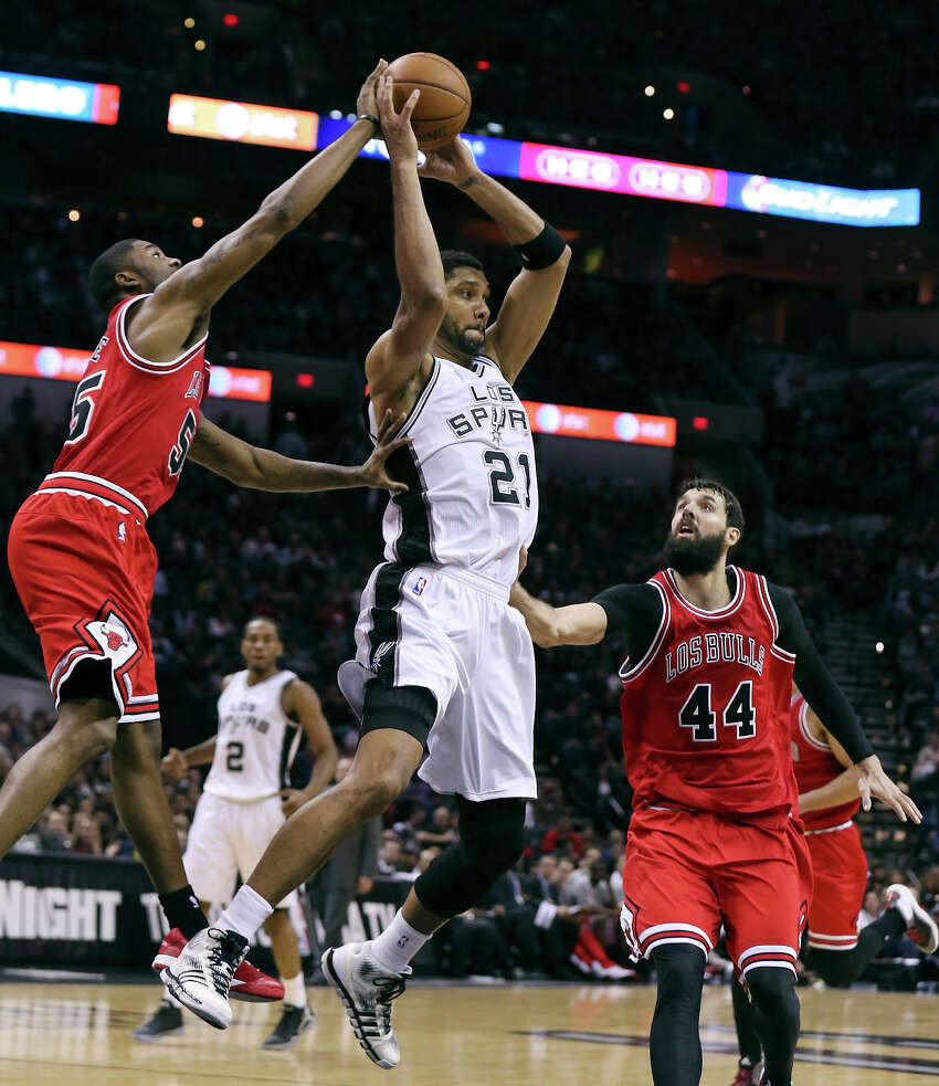 San Antonio Spurs' Tim Duncan looks to pass between Chicago Bulls' E'Twaun Moore (left) and Nikola Mirotic during first half action Sunday March 8, 2015 at the AT&T Center.