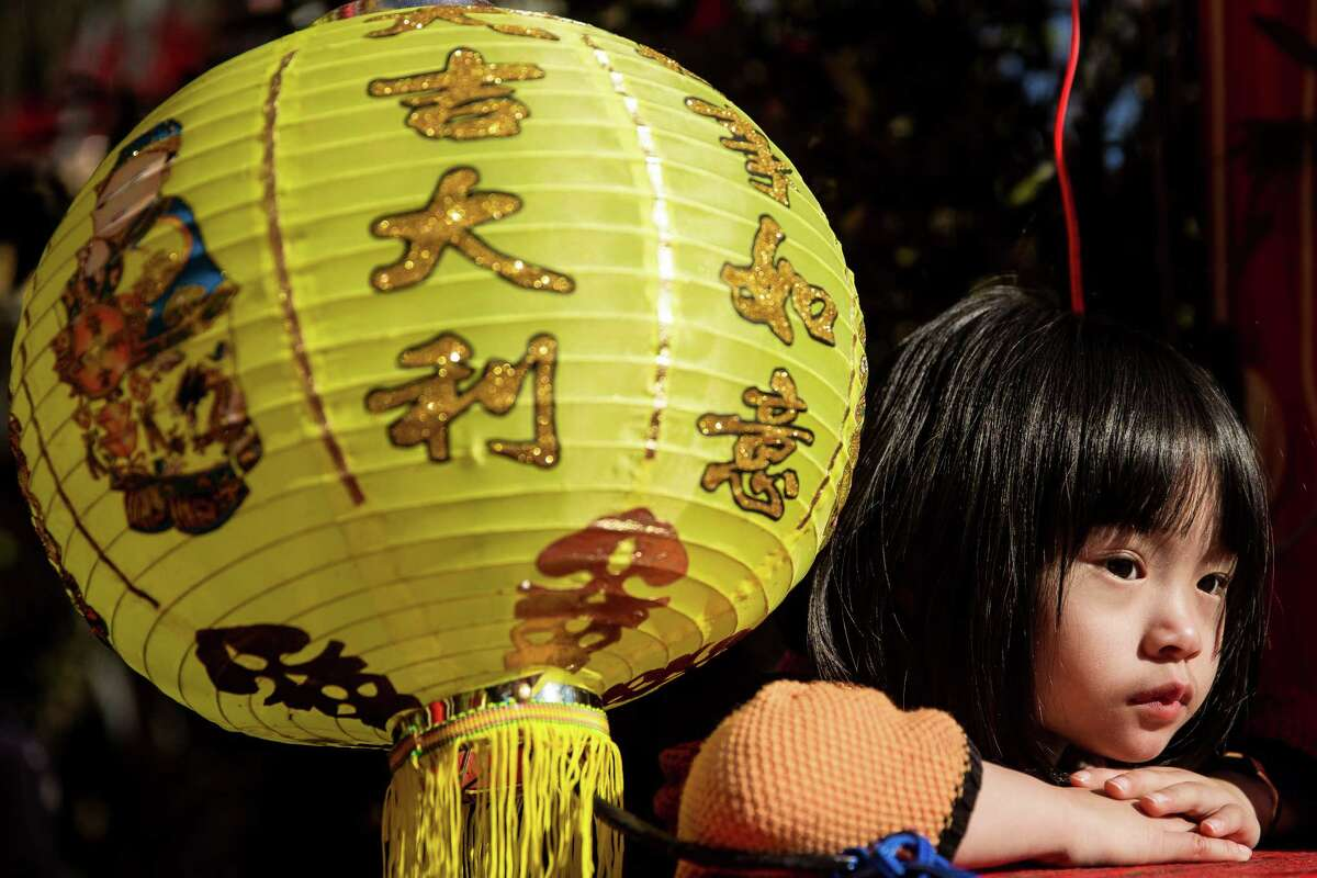 A young girl watches the Dragon Dance during the First Full Moon Ceremony, photographed March 8, 2015, at the Ksitigarbha Temple in Lynnwood, Washington.