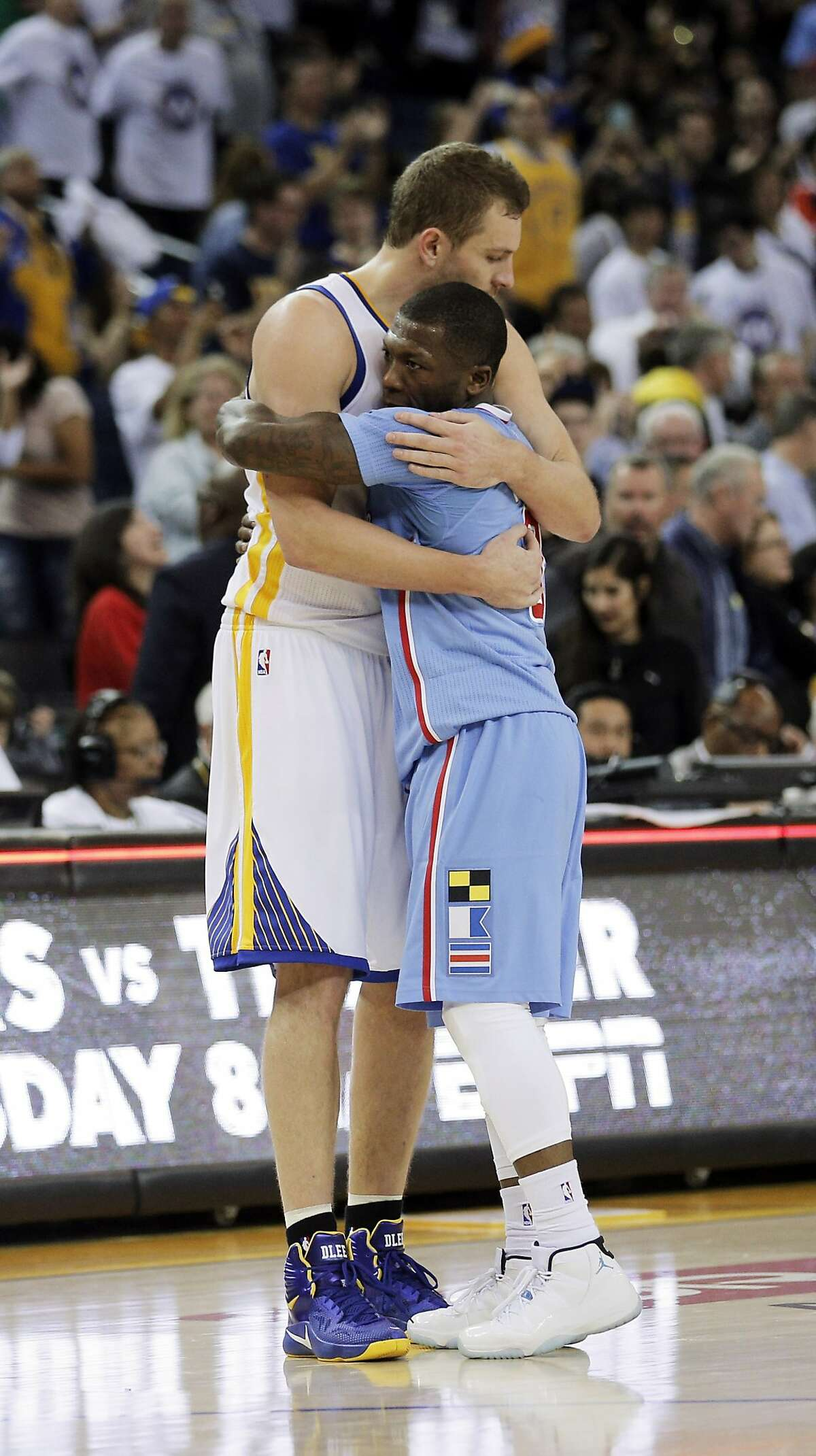 David Lee (10) hugs Nate Robinson (8) after the Warriors defeated the Clippers 106-98. The Golden State Warriors played the Los Angeles Clippers at Oracle Arena in Oakland, Calif., on Sunday, March 8, 2015.