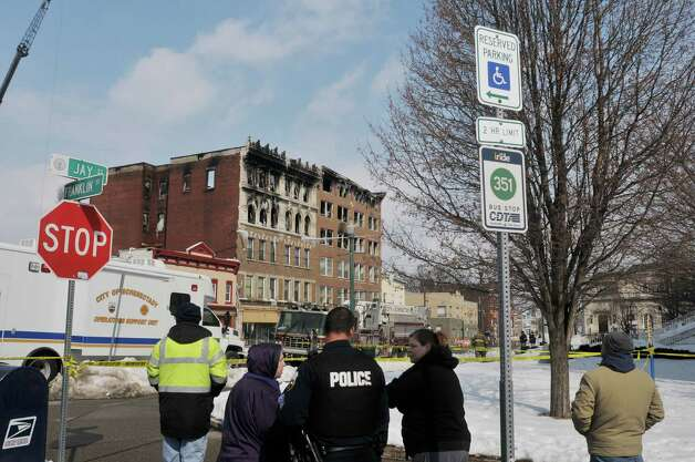 People look over the scene of the apartment buildings on Jay St. that were damaged by fire, seen here on Sunday, March 8, 2015, in Schenectady, N.Y.    (Paul Buckowski / Times Union) Photo: PAUL BUCKOWSKI / 00030931A