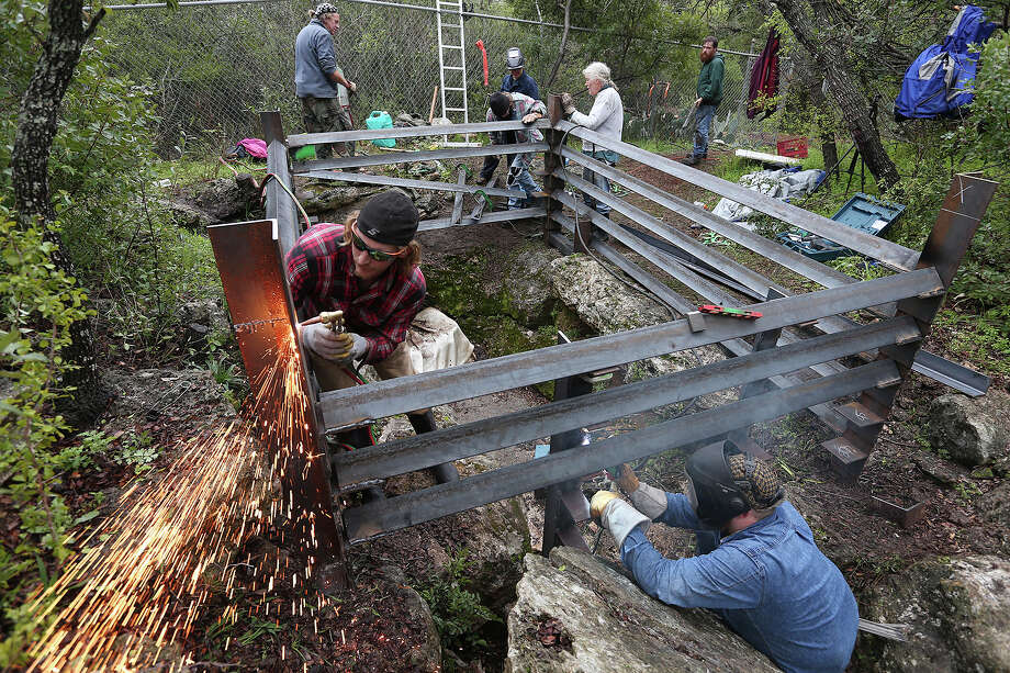 Galen Falgout, left, and Gregg Williams, lower right, help build a gate at the entrance to Ezell's Cave in San Marcos, Sunday, March 8, 2015. Volunteers with the Texas Cave Management Association spent the day working on the gate. The new gate will replace one installed to keep trespassers out of the cave. Unfortunately, it also prevented the bats from entering and exiting very easily. Photo: JERRY LARA, San Antonio Express-News / © 2015 San Antonio Express-News