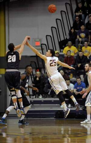 Matt Miller of New Hampshire, left, puts up a shot as Wheeler Baker of UAlbany defends during their America East semifinal game on Sunday, March 8, 2015, in Albany, N.Y.    (Paul Buckowski / Times Union) Photo: PAUL BUCKOWSKI / 00030901A