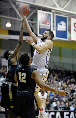 Peter Hooley of UAlbany drives to the basket over a New Hampshire player in their America East semifinal game on Sunday, March 8, 2015, in Albany, N.Y. (Paul Buckowski / Times Union) Photo: PAUL BUCKOWSKI / 00030901A