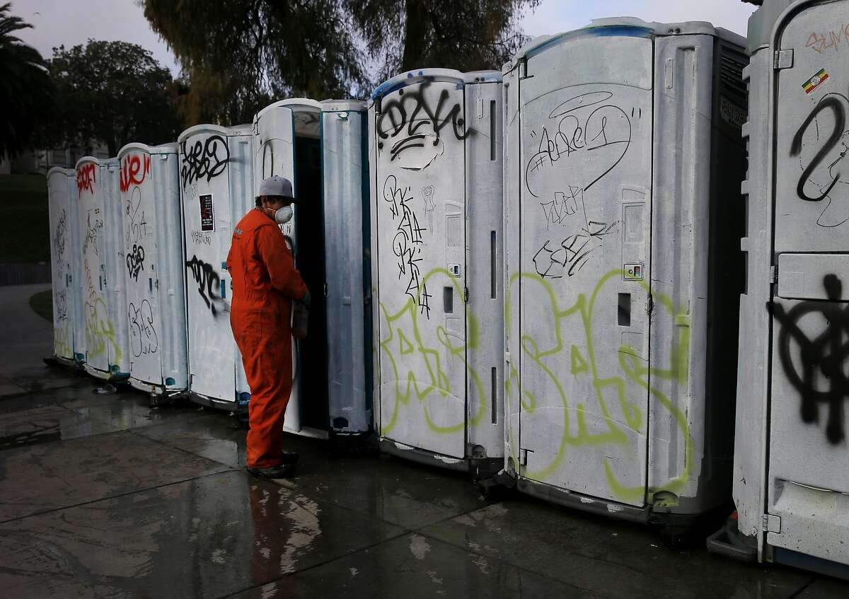 A worker tries to freshen up some portable toilets after a weekend night Sunday March 8, 2015. Dolores Park in San Francisco, Calif. has become a destination for many on a warm winter day, unfortunately the crowds leave a huge trash mess behind, especially on weekends.