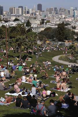 Visitors soak up the sun on the hillsides at Dolores Park in San Francisco, Ca. on Sat. March 7, 2015.