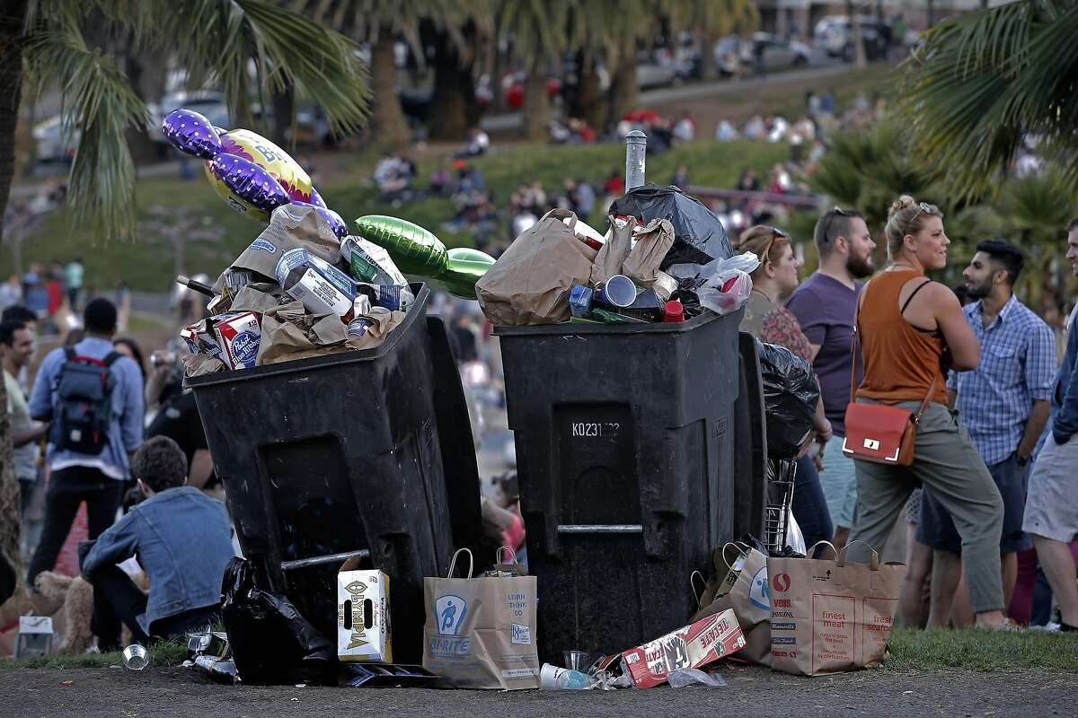 Trash cans are filled to the brim with trash in the late afternoon, at Dolores Park on Sat. March 7, 2015.