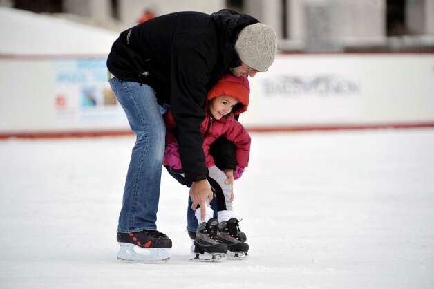 Carlos Mendez of Guilderland helps his daughter, Luisa, 4, to skate at the ice rink at the Empire State Plaza on Sunday, March 8, 2015, in Albany, N.Y.  This was only the second time that Luisa was on skates.  Sunday was the last day the ice rink was open for this season.   (Paul Buckowski / Times Union) Photo: PAUL BUCKOWSKI / 00030923A