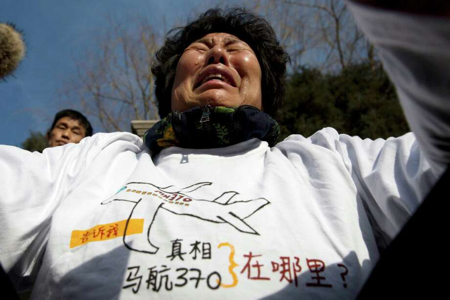 "Liu Guiqiu, whose son was on board Malaysia Airlines Flight 370 that went missing, cries as she protests near the Malaysian Embassy in Beijing on the one year anniversary of the plane's disappearance, Sunday, March 8, 2015. Families of the 239 people on board the plane on Sunday marked the anniversary of the plane's disappearance, vowing to never give up on the desperate search for wreckage and answers to the world's biggest aviation mystery. Words on the T-shirt read ""Truth Malaysia Airlines 370 where is it?""(AP Photo/Ng Han Guan) Photo: Ng Han Guan, STF / Associated Press / AP"