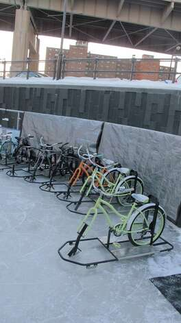 In a Feb. 25, 2015 photo, line of ice bikes await riders at the Ice at Canalside in Buffalo, N.Y. Since the rental bikes debuted in December, Ice Bikes of Buffalo founder Lisa Florczak has gotten inquiries from other cold-weather cities interested in rolling them out next year. (AP Photo/Carolyn Thompson)                                ORG XMIT: RPCT202 Photo: Carolyn Thompson / AP