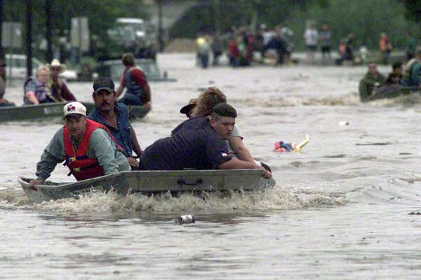 A rainstorm from Oct. 17–19, 1998 set all-time records for rainfall and river levels, resulting in the death of 25 people, and causing more than $500 million damage from the Hill Country to the counties south and east of San Antonio. In this photo, several rescue boats make their way up Esplanade Street in Cuero, Texas. Floodwaters from the Guadalupe River forced the evacuation of residents living close to the river.