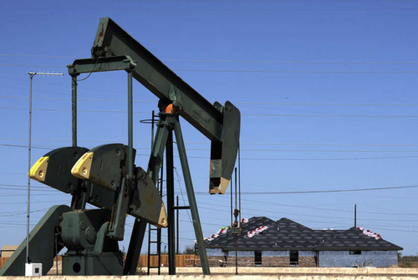 A pump jack works beside the site of new home construction, in Midland, Texas. The West Texas town is in the middle of an oil boom with thousands of workers in need of housing.