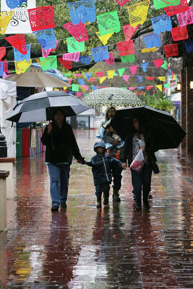 The Perez family from Dallas walks around Market Square, Monday, March 9, 2015. Rain kicked off the start of Spring Break but is expected to taper off by Tuesday. Photo: JERRY LARA, San Antonio Express-News / © 2015 San Antonio Express-News