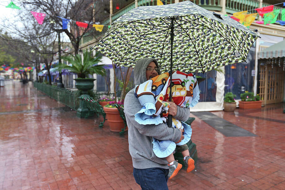 Anthony Perez, from Dallas, carries his son, Anthony, Jr. while walking around Market Square, Monday, March 9, 2015. Rain kicked off the start of Spring Break but is expected to taper off by Tuesday. Photo: JERRY LARA, San Antonio Express-News / © 2015 San Antonio Express-News