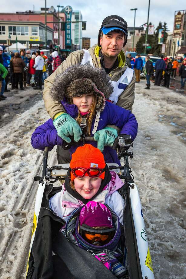Musher Ray Redington waits for his turn at the starting line during the ceremonial start of the Iditarod sled dog race in Anchorage, Alaska, on Saturday, March 7, 2015. With him, from top to bottom, are his daughter, Ellen Redington, 8, niece, Emaliy Flodin, 18, and Iditarider Katie Winfield, 5. (AP Photo/Alaska Dispatch News, Loren Holmes)  KTUU-TV OUT; KTVA-TV OUT; THE MAT-SU VALLEY FRONTIERSMAN OUT Photo: Loren Holmes, Associated Press