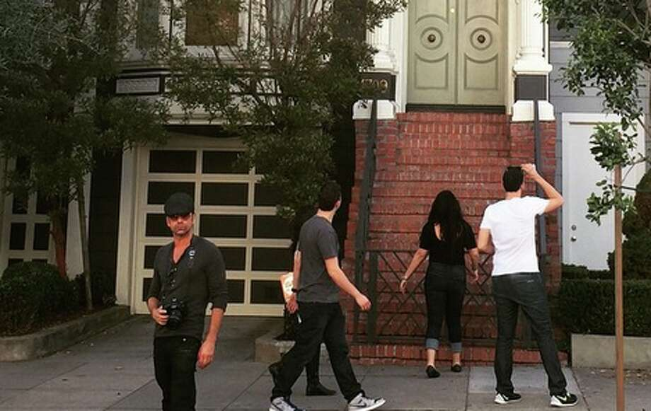 Everywhere you look, everywhere you go...there are people standing around the 'Full House' house in lower Pacific Heights. And look, there's John Stamos standing right out front.