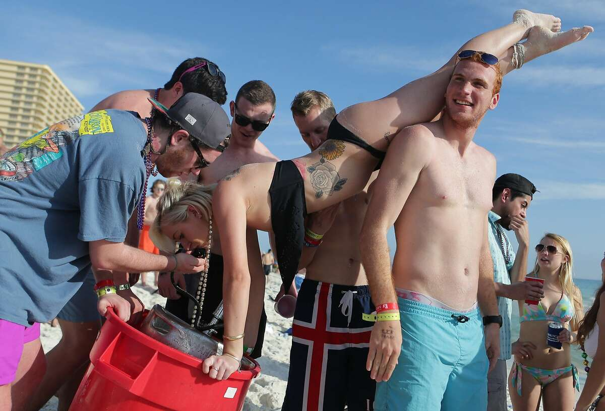 OUT OF CUPS? NO PROBLEM! Spring breakers help a young woman drink directly from the keg in Panama City Beach, Fla.