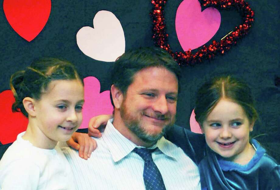 Scott MacDonnell pauses with his daughters, Anna, 8, left, and Brynn, 5, for a moment to have a keepsake photograph taken at the annual Girl Scout Sweetheart Dance, co-sponsored by Girl Scout troops 40237 and 40238 at New Milford High Schoo,l Feb. 27, 2015. Photo: Deborah Rose / The News-Times