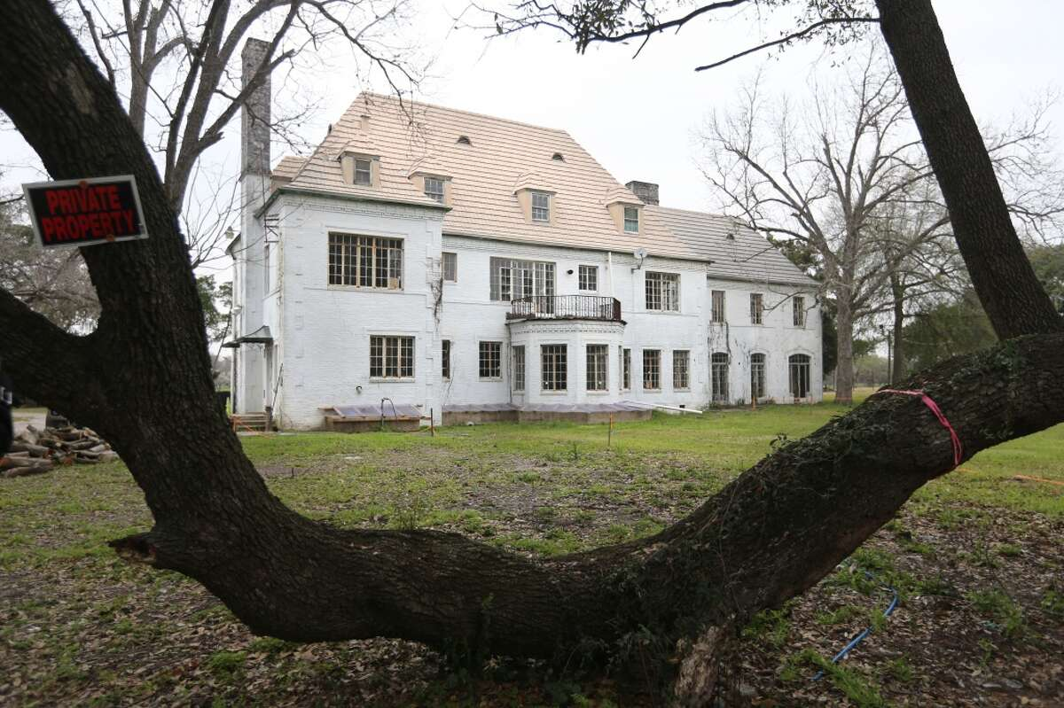 An old oak tree frames the Weingarten mansion from the south side of the property in Riverside Terrace.