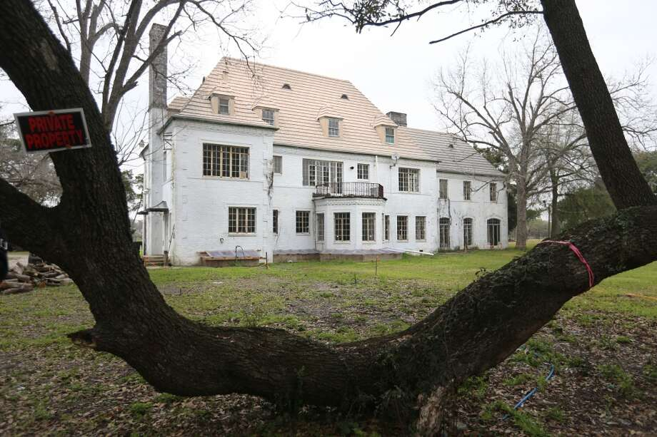 An old oak tree frames the Weingarten mansion from the south side of the property in Riverside Terrace. Photo: Mayra Beltran, Houston Chronicle