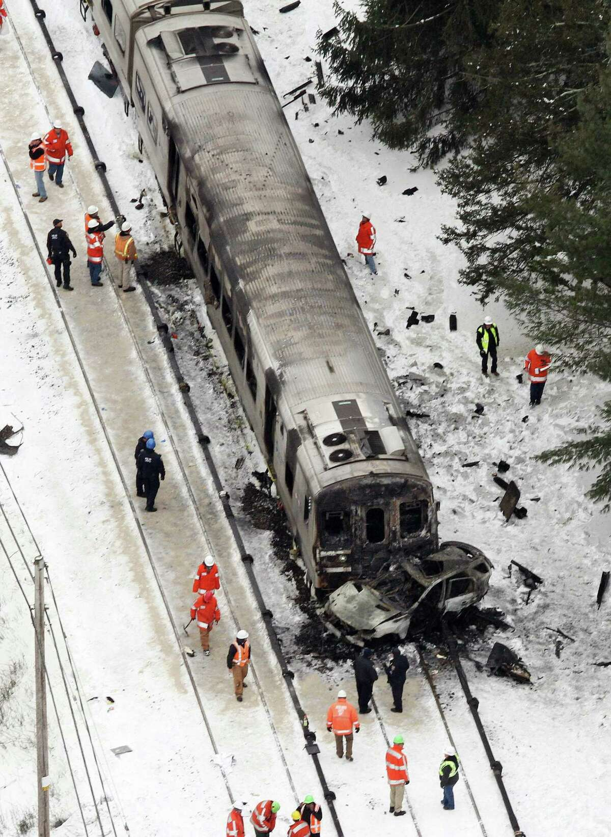 In this aerial photo, personnel from various agencies work the scene of a deadly SUV and commuter train accident in Valhalla, N.Y., Wednesday, Feb. 4, 2015. The packed Metro-North Railroad train slammed into a SUV on the tracks and erupted into flames Tuesday night, killing some and injuring others, sending passengers scrambling for safety, authorities said. (AP Photo/The Journal-News, Frank Becerra Jr.)