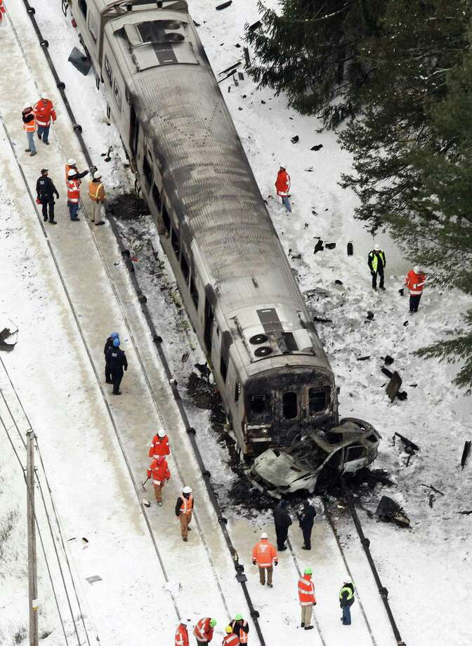 In this aerial photo, personnel from various agencies work the scene of a deadly SUV and commuter train accident in Valhalla, N.Y., Wednesday, Feb. 4, 2015. The packed Metro-North Railroad train slammed into a SUV on the tracks and erupted into flames Tuesday night, killing some and injuring others, sending passengers scrambling for safety, authorities said. (AP Photo/The Journal-News, Frank Becerra Jr.) Photo: Frank Becerra Jr., Associated Press / Connecticut Post Contributed
