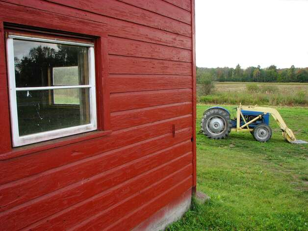 A view of a barn and tractor on land that the town of Clifton Park will purchase the development rights to is seen here during a press conference by the town of Clifton Park in Ballston Lake, NY on Monday, Oct. 5, 2009.   Town officials announced their plan to spend $325,000 to purchase the development rights on a 59-acre farm on Hubbs Road in Ballston Lake.  (Paul Buckowski / Times Union) Photo: PAUL BUCKOWSKI / 00005778A
